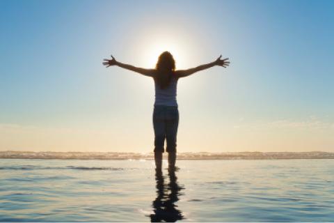 朝日を背景の女性水上シルエット